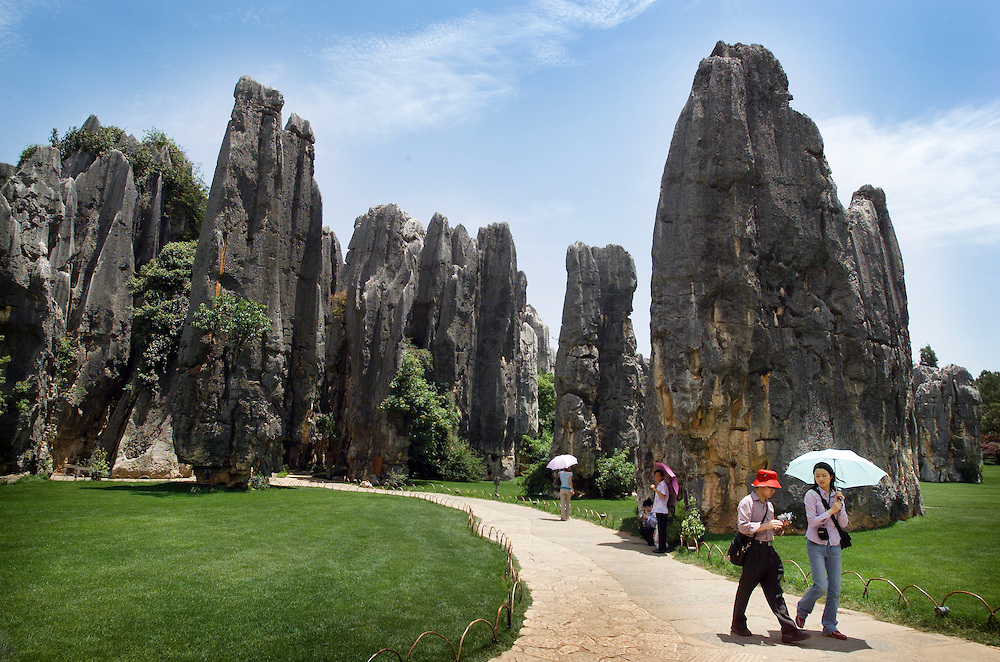 A couple strolles down a path in a groomed section of the Stone Forest (Shilin) China Yunnan province